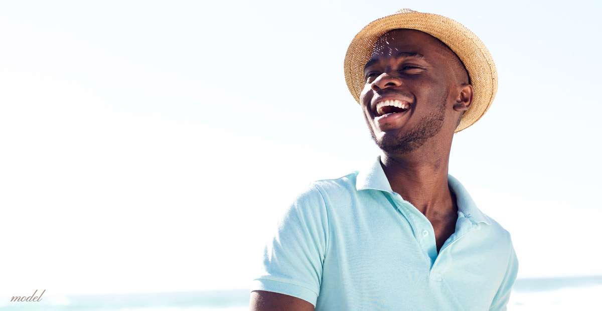 Smiling man on the beach. (model)