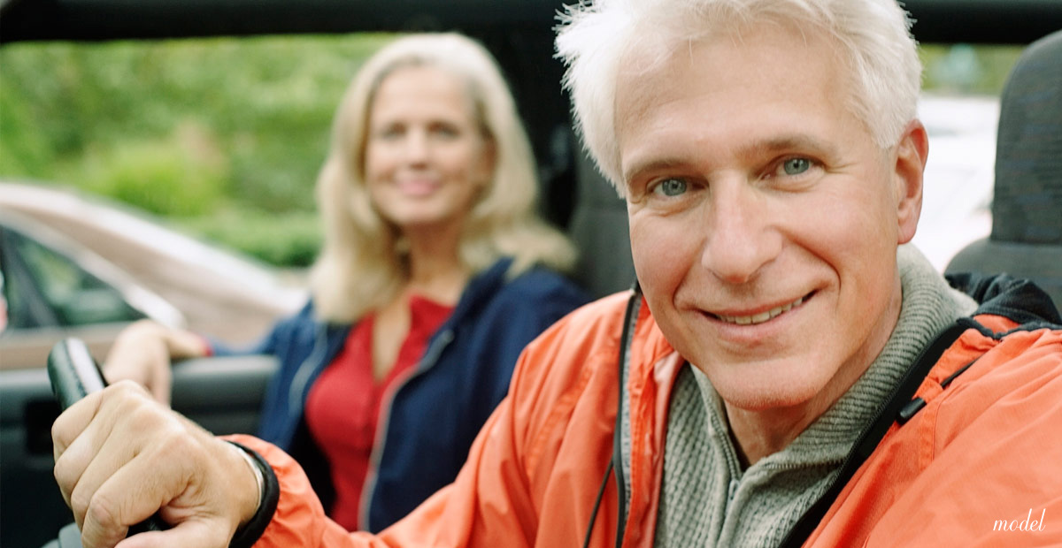 Attractive man with a lifted face enjoying a drive with his wife.