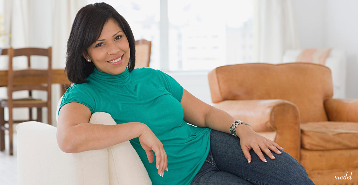 Attractive woman lounging on the couch after successful weight loss. (Model)